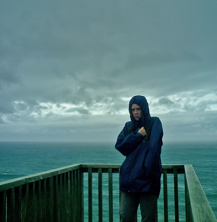girl freezing in gale force winds with stormy sea behind her - nugget point new zealand