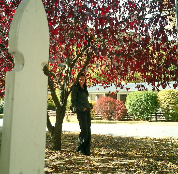 Girl standing in shade of scarlet tree - Arrowtown New Zealand