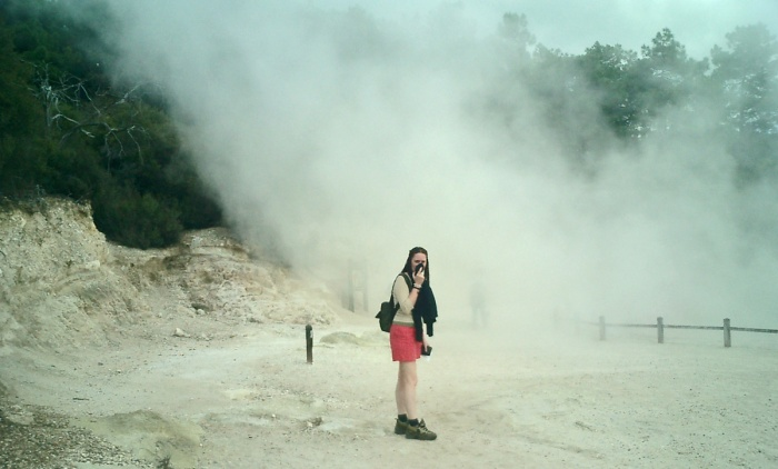 Girl stands in clouds of stinking sulphur steam at Wai-O-Tapu New Zealand