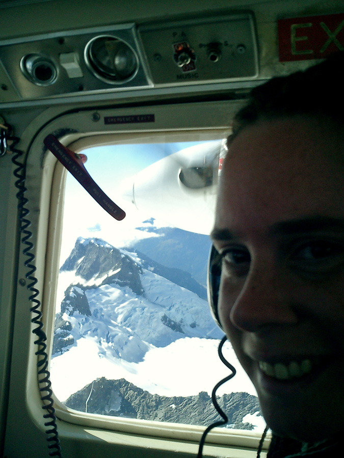 girl wearing aircraft headphones with view of mountain beyond