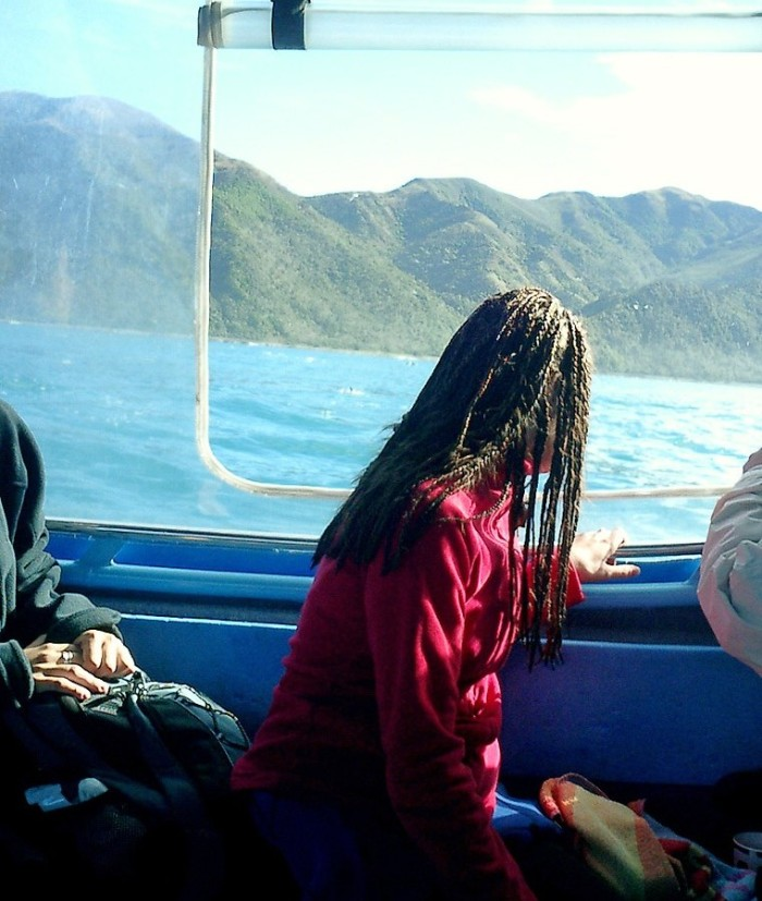 Girl with dreads gazes from boat to shore of south island New Zealand - Oj