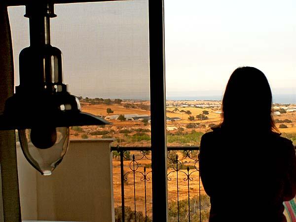 Travel photo Cyprus remote villa on edge of mountains girl gazing at distant horizon