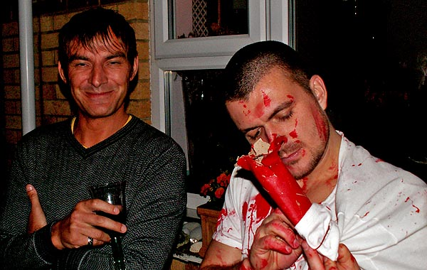 Halloween Party Bristol UK man inspects severed arm bone made of toilet paper tube