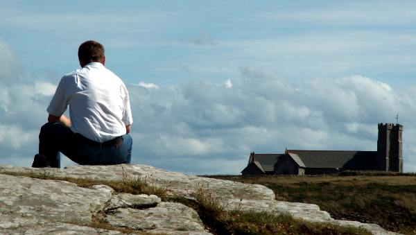 Cornwall England - travel photo - man contemplates medieval church