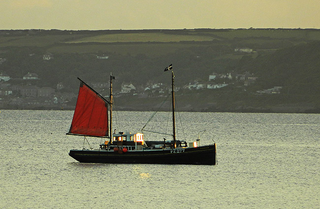 a schooner flying red sail anchored off Cornish coast and St Michael's Mount