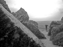 Broken medieval walls and solitary figure with umbrella in rain