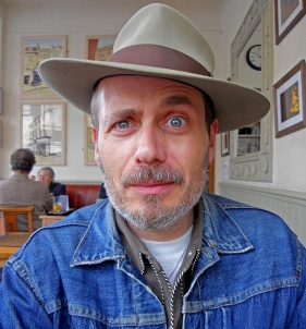 Man with blue eyes wearing a hat and denim Boston Tea Party Cafe Bath