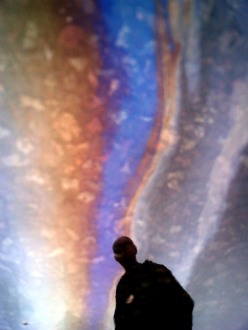 Oil slick on water with silhouette of man