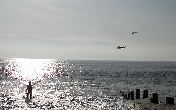 Hayling Island - David J Rodger standing in ocean waving at helicopter and bi-plane
