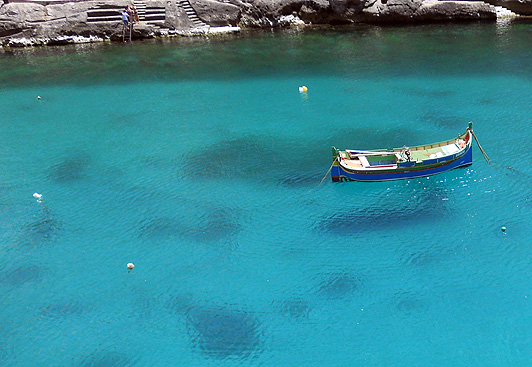 Malta Gozo Xlendi a fishing boat hovering on crystal clear waters