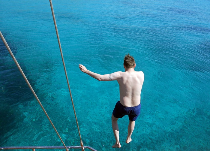 Malta - Kamino - Blue Lagoon - David J Rodger jumping off bow of a yacht