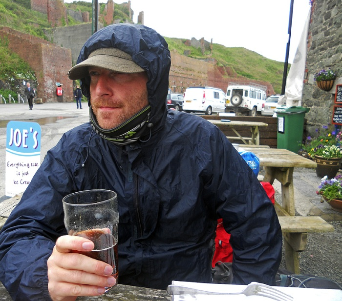 David J Rodger having fish and chips and pint of ale in rain at Porthgain