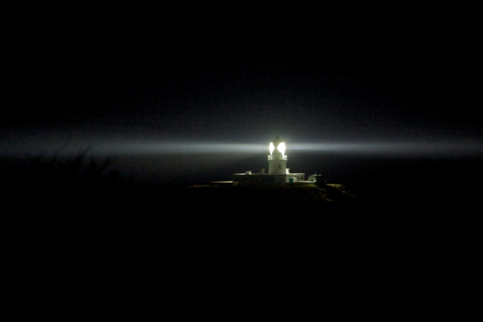 Strumble Head Lighthouse set dramatically against the night sky a beam of light circling photo by Hagen Landsem