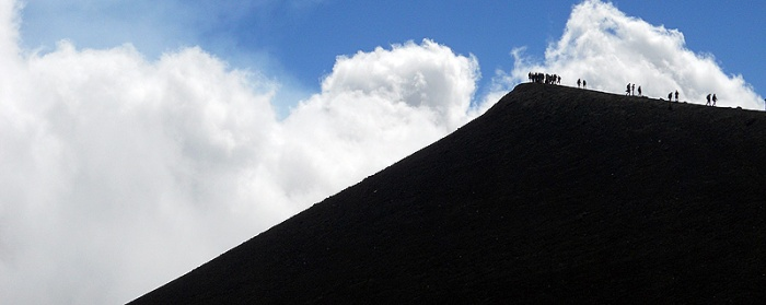 Travel photo Sicily Mount Etna figures clamber along ridge of volcanic crater 3000 metres Torre del Filosofo by David J Rodger