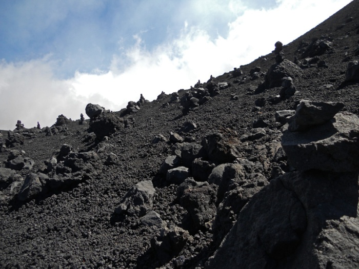 Travel photo Sicily mount Etna - inukshuks built from volcanic pebbles and stones creating alien landscape on side of Torre del Filosofo by David J Rodger