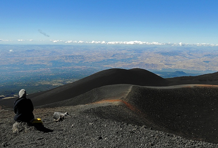 Travel photo Sicily Mount Etna lone figure sits on volcanic rock gazing out at distant horizon by David J Rodger