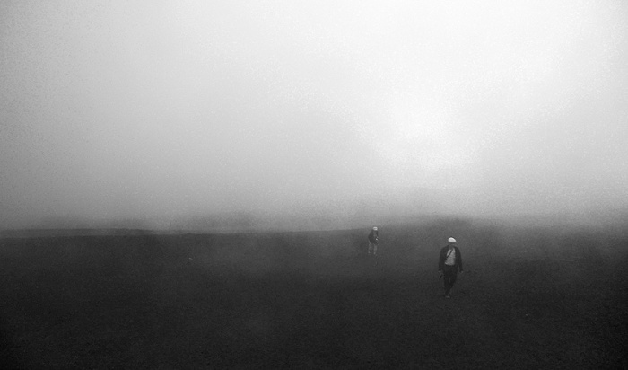 Travel photo Sicily Mount Etna two figures stagger through clouds at 2500 metres from gondola station towards Torre del Filosofo by David J Rodger