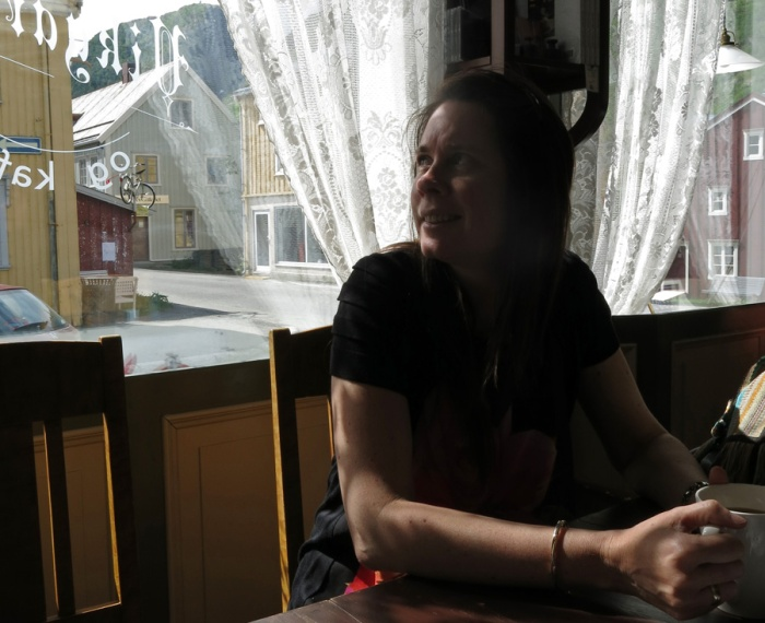Travel photo girl sits in quaint cafe in historical Sjøgata - Sea Street - in Mosjøen, Norway   Photo by David J Rodger