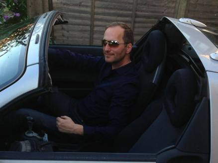 David J Rodger sitting in his tea-tray with a sewing machine in the back - Roadster