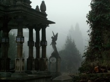Statues in the mist within cemetery