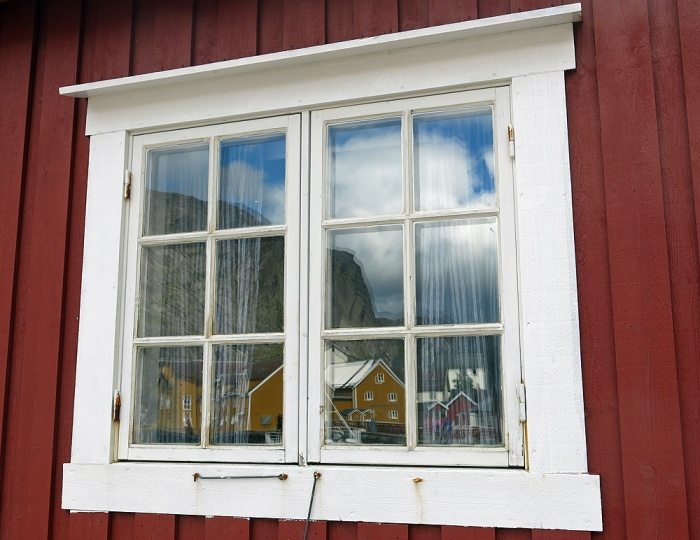 travel photo arctic circle  Norway - white wooden window frame in red painted weatherboard image copyright David J Rodger