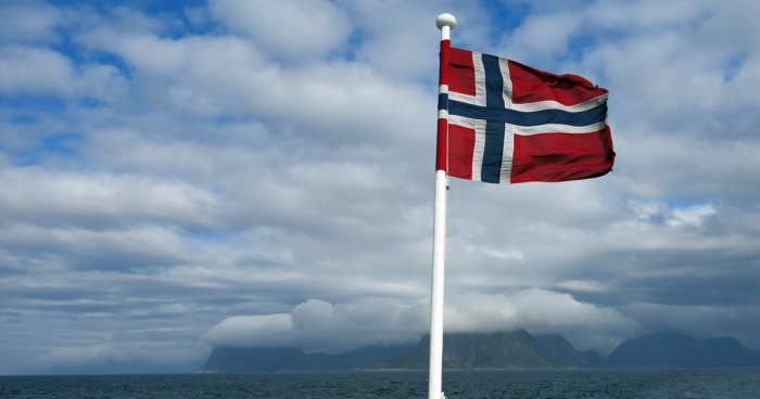 Travel photo - Norway view of Senja Island from sea - low clouds hugging mountain tops - Norwegian flag flapping in sea breeze - copyright David J Rodger