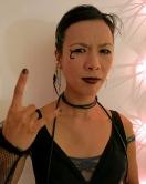 Cyberpunk goth girl shows devil's horns Photo by David J Rodger
