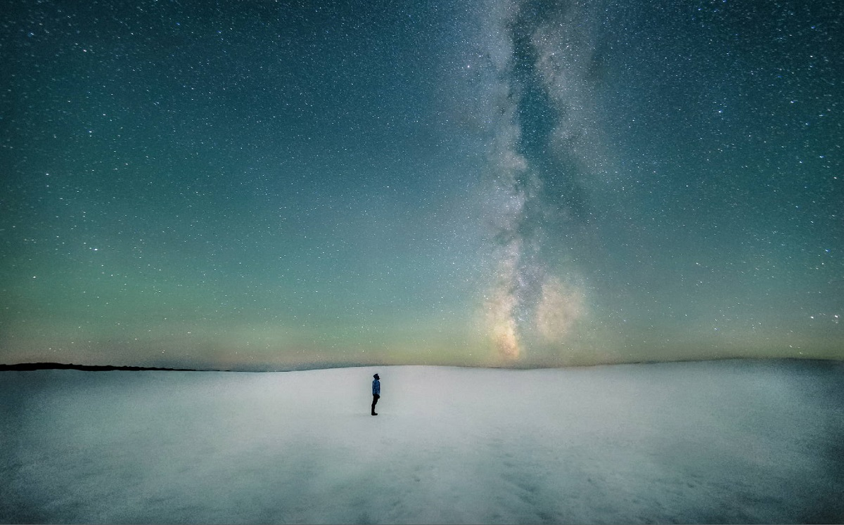 cthulhu mythos inspiration - isolated figure stands alone before the stars of the universe on a frozen landscape