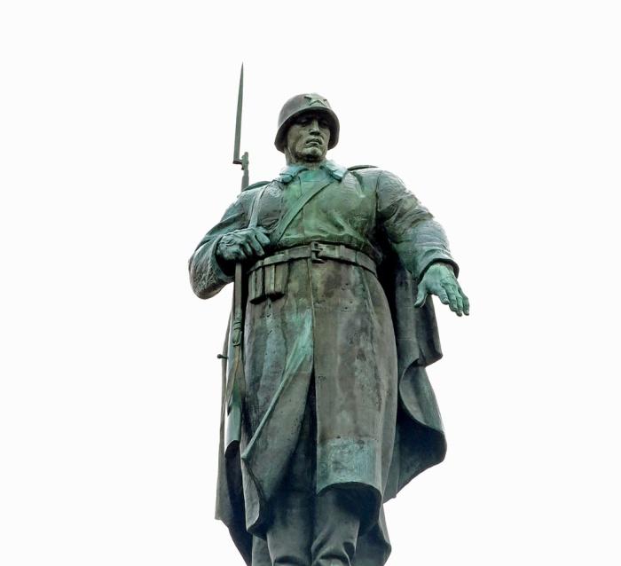 Imposing statue of a soldier atop the Soviet War Memorial in the Tiergarten Berlin