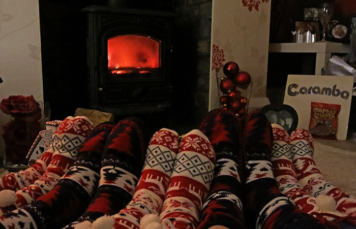 Warm woollen slippers and feet in front of a roaring wood burning stove - photo by David J Rodger - my feet are in the middle