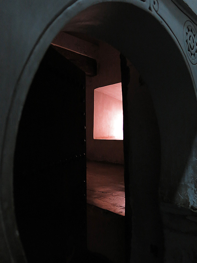 Morocco Marrakech Ben Youssef Medersa darkened room lit by eerie sunlight viewed through medieval door and Arabic archway photo by David J Rodger
