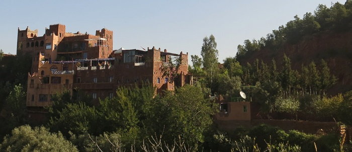Morocco - driving  into foothills of Atlas mountains - wealthy mansion perched on hillside