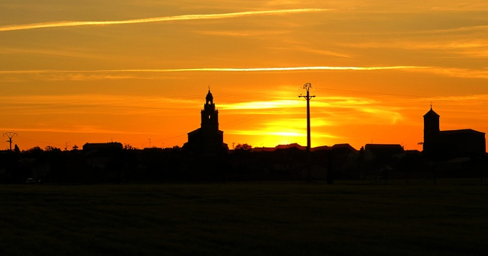 travel photo between Salamanca and Valladolid fiery sunset and church in silhouette