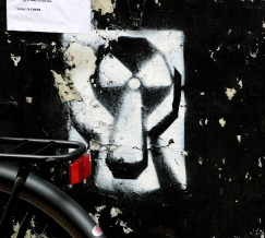 street art graffiti nuclear symbol modified into 3D shape with hands holding itself either side - Amsterdam