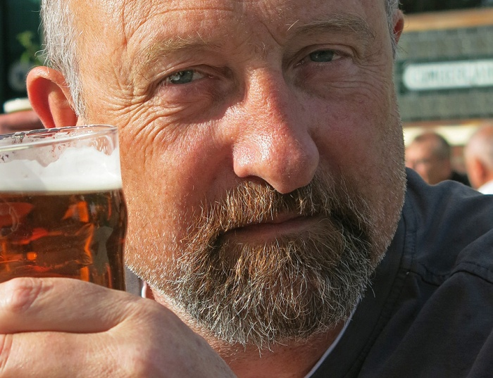 portrait of a white man in 50s with beard and holding a pint