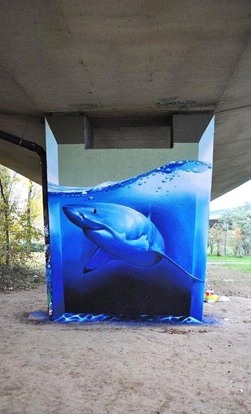 street art graffiti detailed shark and water on concrete pillar