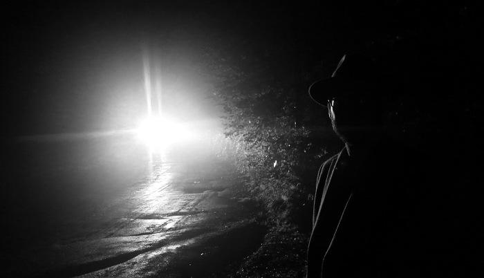 Dark encounter - photo of strange man standing side of lonely country road with car headlights - photo by David J Rodger