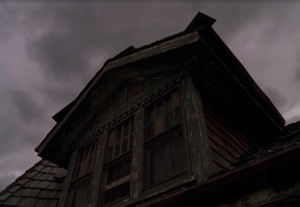 spooky photo of gable window with sinister sky above