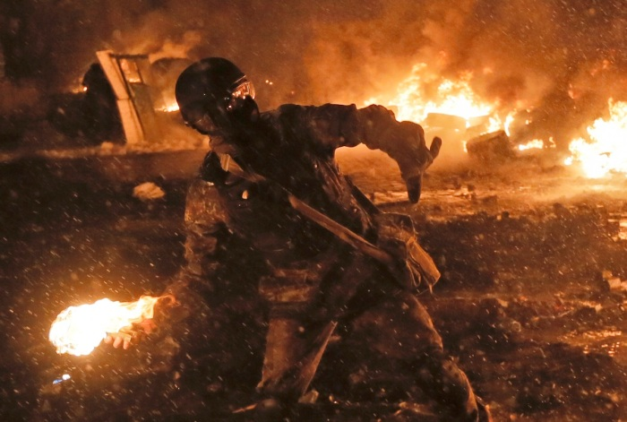 photos of fighting in Ukraine look post-apocalyptic - masked men throws petrol bomb from imgur dot com user magnacookies