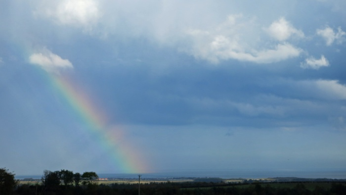 rainbow carves through the sky beyond Northumberland coastline - image David J Rodger