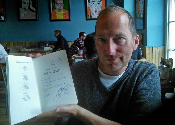 David J Rodger holds signed edition of God Seed, a cyberpunk dark fantasy novel that has been won by military veteran, private defense contractor and horror writer Lincoln Farish